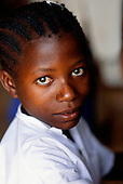 Kala, Tanzania. Schoolgirl in school uniform with braided hair with a safety pin in it.