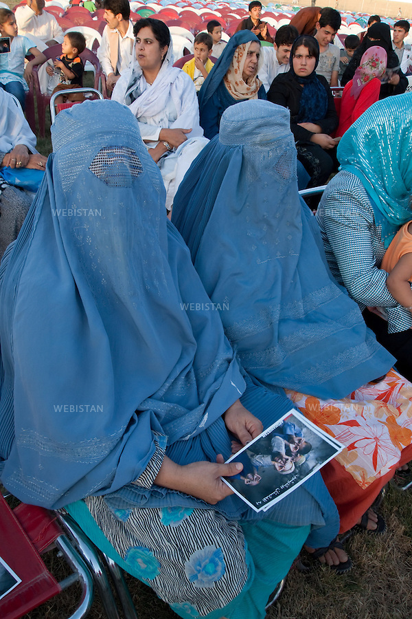 AFGHANISTAN - MAZAR-E CHARIF - 7 aout 2009 : Stade de Mazar-e Charif. Femmes afghanes au concert gratuit du chanteur afghano-americain, Farhad Darya. La femme au premier plan tient une carte postale illustree par une photographie de Reza et signee du chanteur, distribuee a tout le public...AFGHANISTAN - MAZAR-E CHARIF - August 7th, 2009 : Mazar-e Charif stadium. Afghan women at a free concert given by Afghan-American signer Farhad Darya. The woman in the foreground holds a postcard featuring a photograph by Reza. These postcards were autographed by Darya and then distributed to the audience.
