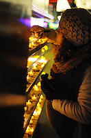 NWA Democrat-Gazette/ANDY SHUPE<br /> Maddi Potter of Rogers writes a message Thursday, Dec. 31, 2015, after lighting a candle in a booth set up for New Year's wishes during the fifth annual Last Night Fayetteville celebration on the town's square. The celebration featured music and performances for all ages on 11 stages leading up to the Hog Drop and fireworks at midnight. Visit nwadg.com/photos to see more photographs from the event.