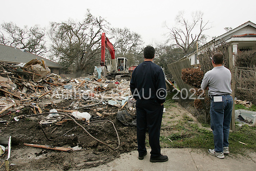 New Orleans, Louisiana.February 21, 2006..Gary Hoffman (50) dressed in dark- and his neighbor Randy Cookmeyer watch as Gary's home is torn down in Lakeview when they were damaged by the the 17th street levee brakes during hurricane Katrina in August 2005. The home had to be destroyed because it was built too low to the ground...