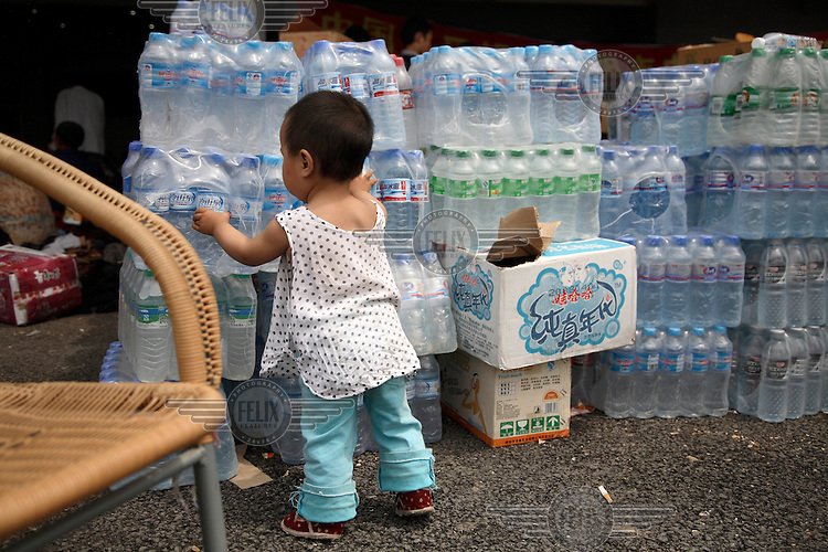 One year old Li Youshi next to crates of bottled water in a temporary shelter at the Jiuzhou Stadium in Mianyang. On the 12/05/2008 an earthquake measuring 8.0 on the Richter scale hit the province of Sichuan.