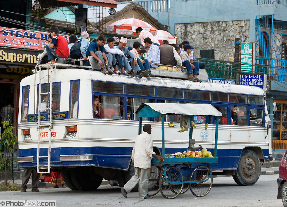 Crowded bus filled to roof, wheeled fruit stand, Pokhara