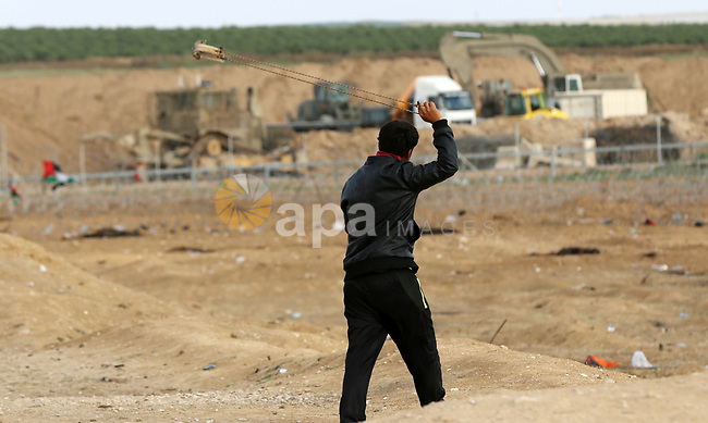 A Palestinian protester uses a slingshot to hurl stones towards Israeli security forces during tents protest where Palestinians demand the right to return to their homeland, at the Israel-Gaza border in east of Gaza City on May 7, 2018. Photo by Yasser Qudih