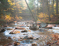 SUBJECT: Pemigewasset River IMAGE: A footbridge crosses the Pemigewasset River in the Franconia Notch in the White Mountains of New Hampshire with dappled sunshine and an abundance of boulders, typical of rivers in this region.