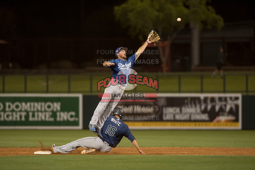 Los Angeles Dodgers second baseman Brandon Montgomery (11) leaps over Evan White (16) as he reaches for a ball during a Minor League Spring Training game against the Seattle Mariners at Camelback Ranch on March 28, 2018 in Glendale, Arizona. (Zachary Lucy/Four Seam Images)
