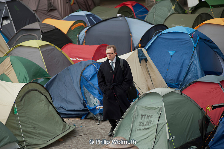 A businessman walks through the Occupy London camp outside St Paul's Cathedral.