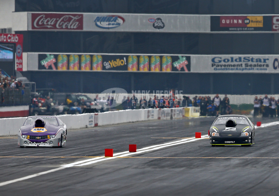 Feb 9, 2014; Pomona, CA, USA; NHRA pro stock driver Vincent Nobile (left) races alongside Dave Connolly during the Winternationals at Auto Club Raceway at Pomona. Mandatory Credit: Mark J. Rebilas-