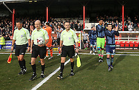 Match officials & Matt Bloomfield of Wycombe Wanderers lead players onto the pitch during the Sky Bet League 2 match between Grimsby Town and Wycombe Wanderers at Blundell Park, Cleethorpes, England on 4 March 2017. Photo by Andy Rowland / PRiME Media Images.