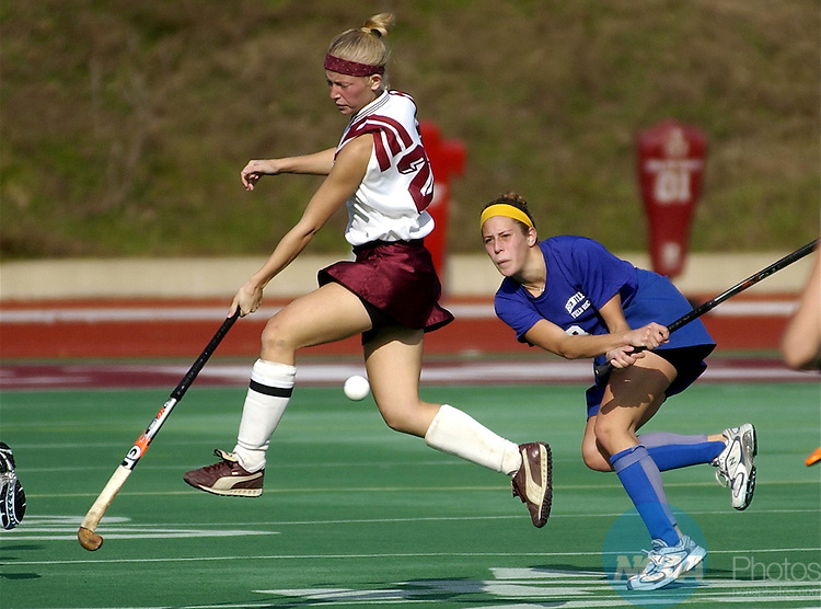 10 NOV 2002:  Bloomsburg University's Shannon Fritz (22) jumps to avoid a ball hit by Bentley College's Kara Bouvier (8) in the first half of the Division II Women's Field Hockey Championship held at Lock Haven University in Lock Haven, Pa.  Bloomsburg University defeated Bentley College 5-0 for the championship title.  Pat Little/NCAA Photos.