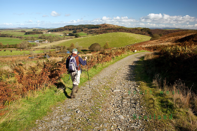 Walking along track from Loch Mannoch and Martyrs Monument with Neilson's Monument on Barstobrick Hill in the distance, Ringford, Galloway, Scotland.