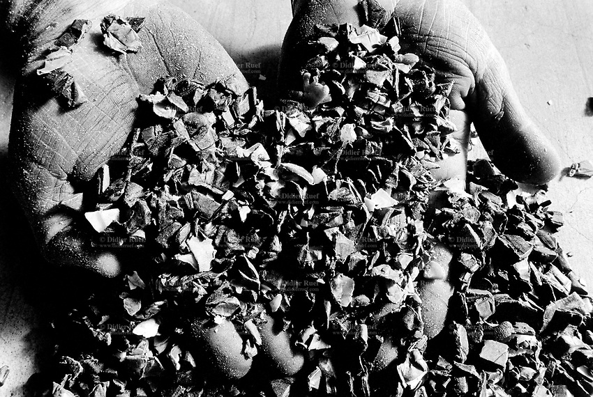 Italy. Bologna Region. Pieve de Cento. Politec (Himont) company.  Cars scrapyard. The polyprophylene bumpers are ground down for recycling. Two hands of a worker.  © 1993 Didier Ruef .