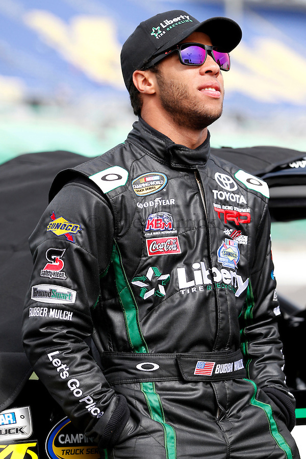 KANSAS CITY, KS - Darrell Wallace Jr., driver of the #54 Liberty Tire Recycling / Ground Smart Rubber Toyota, stands on the grid during qualifying for the NASCAR Camping World Truck Series SFP 250 at Kansas Speedway on April 20, 2013.