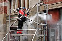Werknemer van de reinigingsdienst in Amsterdam spuit een gevel  schoon