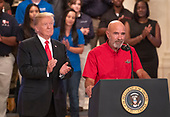 """Carl Greene, DED Road Team Member, American Trucking Associations, right, makes remarks as United States President Donald J. Trump, left looks on prior to the President signing an Executive Order establishing the National Council for the American Worker, which the Trump Administration calls """"an Interagency Council of Administration officials who will focus on crafting solutions to our country's urgent workforce issues"""" in the East Room of the White House in Washington, DC on Thursday, July 19, 2018.<br /> Credit: Ron Sachs / CNP"""