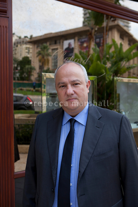 """Eric Elena, member of Monaco's """"Conseil National"""" - the parliament of Monaco-, poses for the photographer outside a boutique in Casino Square, Monte Carlo, Monaco, 18 October 2013. The Sporting d'Hiver building can be seen in the window's reflection. Eric also works for the Société des Bains de Mer (SBM) as a """"chef de table"""" at the casino (which means that he runs a team of croupiers). He's a member of Renaissance, a political party in Monaco which campaigned against the demolition of the Sporting d'Hiver."""