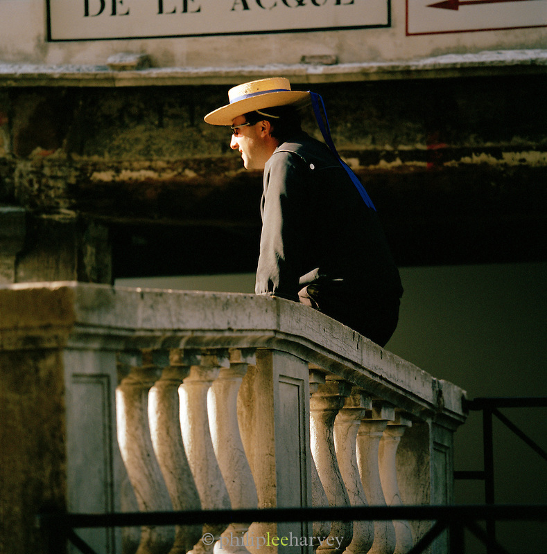 A gondolier, a gondola driver sitting on a wall in Venice, Italy