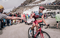 "Maxim Belkov (RUS/Katusha) catching a 'gazetta' (for the downhill) up the gravel roads of the Colle delle Finestre that reads ""The ruthless climb that loves pink""<br /> <br /> stage 19: Venaria Reale - Bardonecchia (184km)<br /> 101th Giro d'Italia 2018"
