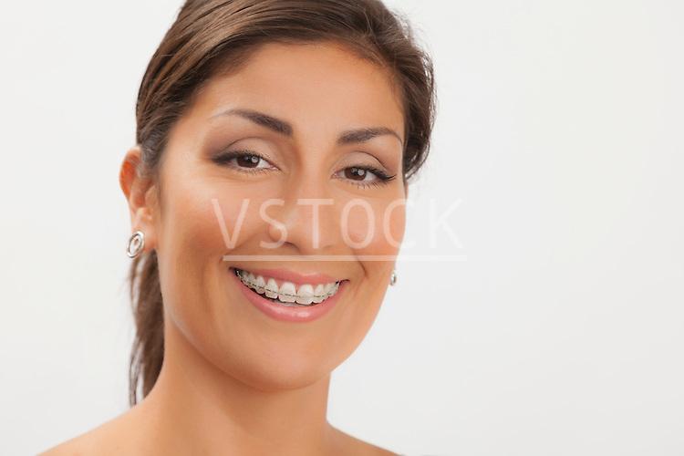 Studio shot portrait of mature woman wearing braces