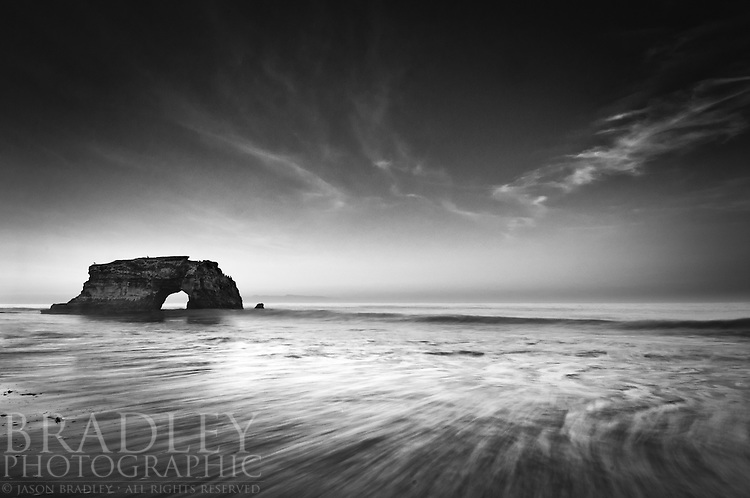 """This image opened a recently published article called """"Why Choose Black and White,"""" in Outdoor Photographer magazine.  It is featured in the August 2011 annual Black & White issue, and highlights how the absence of color opens the door to new possibilities about a scene.  Instead of featuring color, focusing on other things like textures, shapes, and fine tonal gradations can become primary compositional tools...I shot this at dawn, at Natural Bridges State Park in Santa Cruz, CA.  I used a tripod and a Singh-Ray, 3-stop, hard edge, graduated neutral density filter, and a slow shutter speed of 1/5 of a second to create the water movement.  The trick was to hit the shutter just as the incoming wave was starting to recede.  The water moving back in created the effect and texture of the lines leading into the center of the frame."""