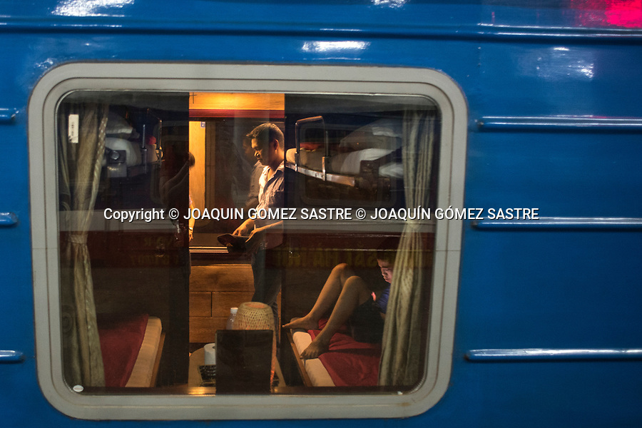 Passengers in one of the compartments of the night train to LAO CAI in the station of Hanoi (Vietnam)<br /> HANOI-VIETNAM