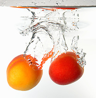Apricots fruits splashing underwater, white background, studio