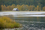 Idaho, North, St. Maries. Morning mist rises off a roadside pond with rustic barn in early autumn.