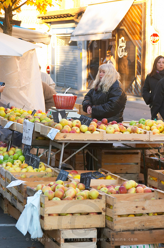 Apples of varying kinds in wooden crates for sale at a market stall at the market in Bergerac, a woman selling. Bergerac Dordogne France