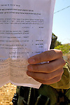 An Israeli soldier holds a document classifying the area as a closed military zone to prevent his face being photographed during a non-violent demonstration in the West Bank village of Beit Ummar near Hebron on 10/07/2010.
