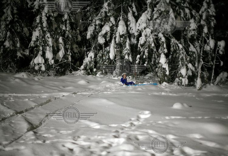 Oscar Ø. Mortensen (10)  ski jumping in Schrøderbakken, nearly ends up in the forest after landing.  Near the center of Oslo, Norway.