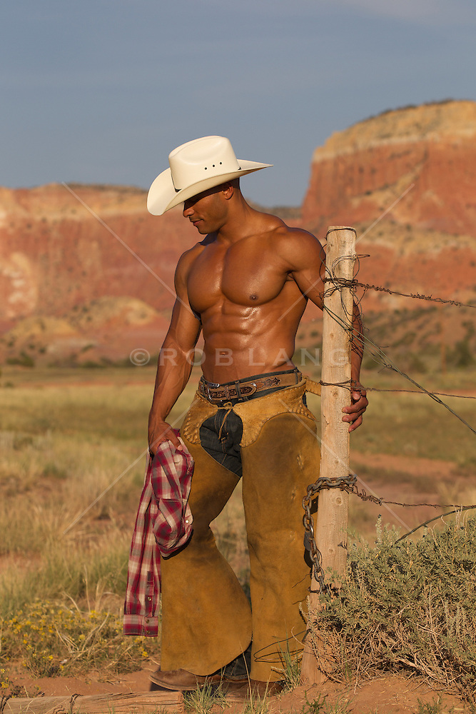 shirtless cowboy wearing chaps exposing his abs and muscular chest outdoors