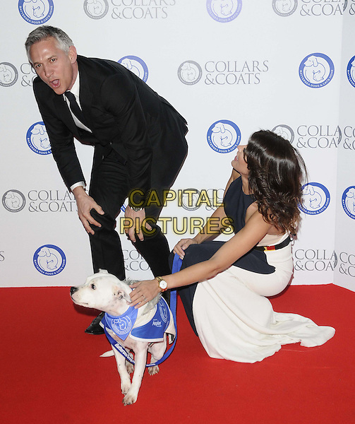 Gary Lineker & Danielle Lineker.Attending the Battersea Dogs & Cats Home 'Collars & Coats Gala Ball 2012' held at Battersea Evolution, London, England, UK, 8th November 2012..full length black suit tie white beige nude dress navy blue belt colour block married couple husband wife long maxi dog bending funny stroking .CAP/CAN.©Can Nguyen/Capital Pictures.
