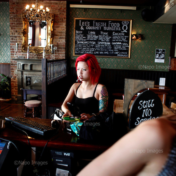 Red haired girl smoking a cigarette at a pub in Brighton, July 2010.(Photo by Piotr Malecki / Napo Images)<br /> <br /> Pub w Brighton, 07/2010<br /> Fot: Piotr Malecki / Napo Images