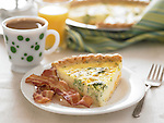 A slice of quiche with bacon and a cup of coffee.