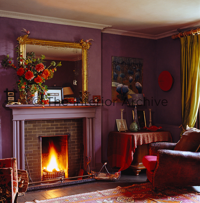 The roaring fire casts a warm glow in this aubergine-coloured sitting room