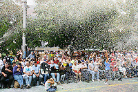 Switzerland. Canton of Neuchâtel. Neuchâtel. Grape Harvest Festival. During the flower parade (corso), confetti are thrown from a vehicle to the public, seated on the side of the road. © 2006 Didier Ruef