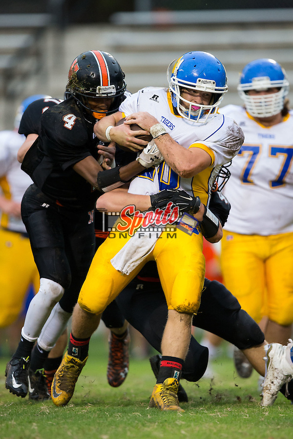 Cody Reece (20) of the Mount Pleasant Tigers is wrapped up by Sam Newhouse (48) of the Northwest Cabarrus Trojans during first half action at Trojan Stadium October 1, 2015, in Concord, North Carolina.  The Tigers defeated the Trojans 42-0.  (Brian Westerholt/Sports On Film)