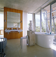 The contemporary master bathroom is light and airy with a floor of terrazzo slabs