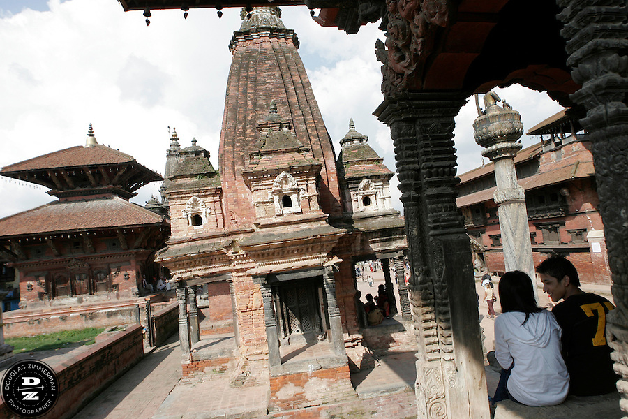 A couple sits together among the temples and monuments of Patan's Durbar Square in Patan, Nepal.  Photograph by Douglas ZImmerman