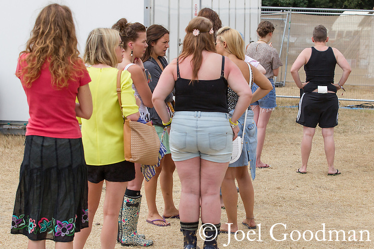 © Joel Goodman - 07973 332324 . 20/07/2013 . Suffolk , UK . Women queue for the toilets . One carries toilet paper in the back of her shorts . The Latitude music and culture festival in Henham Park , Southwold . Photo credit : Joel Goodman