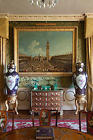 A painting of Piazzo San Marco in Venice hangs above a colourful and elaborately inlaid chest of drawers in the drawing room