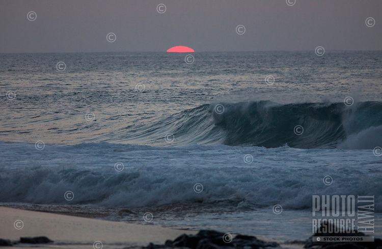 The last bit of sun setting on the horizon over the ocean with a wave breaking at Rock Piles beach on the North Shore, O'ahu