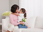 USA, Illinois, Metamora, mother and daughter (4-5) embracing on sofa