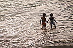 Young girls holding hands - children playing in the sea at sunset, Store bay, Tobago