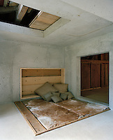 The walls and floors of the bedroom are made of cast concrete with a sunken double bed covered in a cow-hide throw and a pile of rough linen scatter cushions