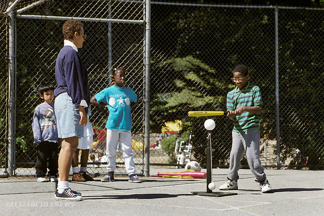 "Oakland, CA Adaptive P.E. teacher supervising learning handicapped children with ""T"" ball play"