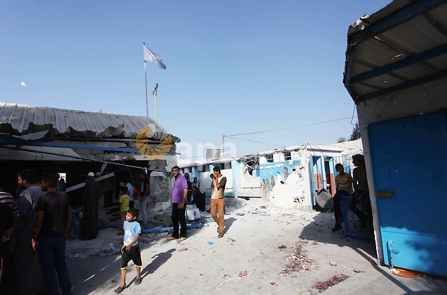 """Palestinian men inspect the damage at a UN school at the Jabalia refugee camp in the northern Gaza Strip after the area was hit by Israeli shelling on July 30, 2014. Israeli bombardments early on July 30 killed """"dozens"""" of Palestinians in Gaza, including at least 16 at a UN school, medics said, on day 23 of the Israel-Hamas conflict. Photo by Ashraf Amra"""