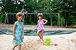 "Identical twin sisters Piper (purple) and Katie, 5, play at McClatchey Park in Atlanta May 14, 2010. Piper said the best part about having a sister is ""giving my sister hugs and kisses."" Katie said the best part about having a sister is ""kissin' her and huggin' her."""