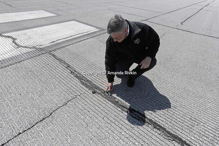 "Airport Manager Andy Jones pulls rocks from a tar-filled crack on the runway at the Elkhart Municipal Airport in Elkhart, Indiana on April 8, 2009.  As part of the ""bail out"" funds, one of two runways will be repaired; Jones said he had to turn down the request from Air Force One and the president's advance staff, citing the weight of the aircraft and the fragile state of the runways, to land at Elkhart Municipal Airport."