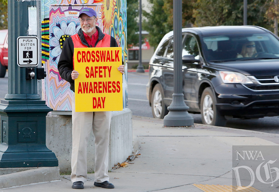 NWA Democrat-Gazette/DAVID GOTTSCHALK  City of Fayetteville MayorLioneld Jordan holds signage Wednesday, October 14, 2015 at the intersection of Lafayette Street and College Avenue bringing attention the 12th annual Crosswalk Safety Awareness Day. Individuals, city of Fayetteville personnel and local groups sharing the event message It's Not a Choice, It's the Law! at intersections though out the city.