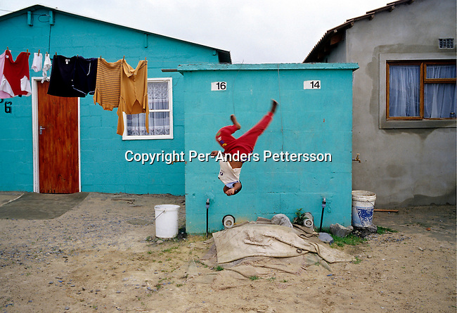 KHAYELITSHA, SOUTH AFRICA - OCTOBER 1: (GERMANY, SOUTH AFRICA AND ITALY OUT) An unidentified boy play outside his family home on October 1, 2004 in Khayelitsha, the biggest black township, about 20 miles outside Cape Town, South Africa. It's estimated that over one million people live here, most of them under appalling conditions in shacks with no running water or electricity. The township was founded in 1984 and it still attracts people from the rural areas that look for work in Cape Town. Most of the people don't find work and the lucky few are paid low wages used mostly as maids and day laborers..(Photo: Per-Anders Pettersson/Getty Images).....